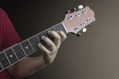 一个年轻吉他弹奏者的左手的特写镜头紧跟在一把声学吉他后面的 免版税库存图片