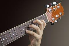 一个年轻吉他弹奏者的左手的特写镜头紧跟在一把声学吉他后面的 库存图片