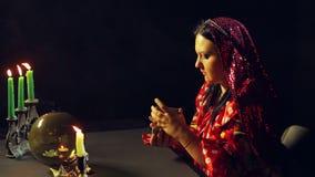 一个年轻吉普赛人在烛光的算命交谊厅拖曳占卜的卡片 股票视频