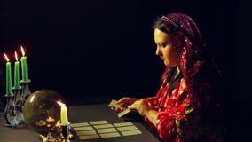 一个年轻吉普赛人在烛光的算命交谊厅计划占卜的卡片在桌上 影视素材