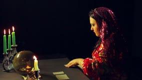 一个年轻吉普赛人在烛光的算命交谊厅计划占卜的卡片在桌上 股票视频