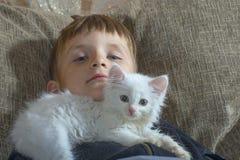 一个年轻和快乐的小男孩使用与在长沙发的一只白色猫 免版税库存图片
