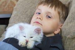 一个年轻和快乐的小男孩使用与在长沙发的一只白色猫 免版税库存照片