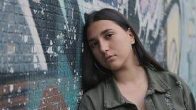 一个年轻哀伤的深色的行家女孩的画象在墙壁附近的有街道画的 股票录像
