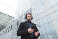 一个年轻商人听到在耳机的音乐并且使用智能手机,当走在城市附近时 库存图片
