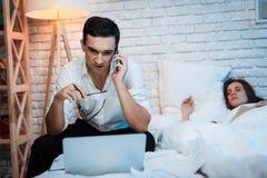 一个年轻商人在电话里在床上说并且在膝上型计算机后在家工作 库存图片