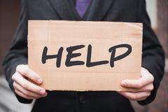 一个年轻商人拿着有题字的'帮助'纸板片剂在他的手上 库存照片