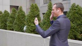 一个年轻商人来与在他的耳朵的无线在一视频通话的耳机和愉快地谈话在智能手机 股票视频
