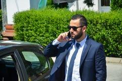 一个年轻商人的严肃的交谈在一条典雅的衣服和领带的 库存照片