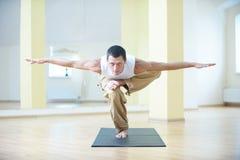 一个年轻大力士在一条腿的asana分开站立有胳膊的在瑜伽演播室 库存照片