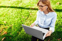 一个年轻女商人戴着眼镜的画象,坐绿草在公园,工作使用膝上型计算机和无线headph 库存图片