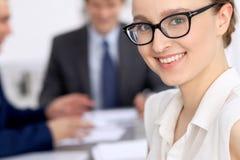 一个年轻女商人的画象反对一个小组的商人在会议上 库存照片