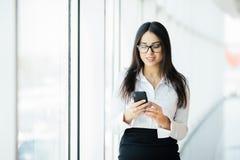 一个年轻女商人键入的文本电话的画象反对全景窗口的 到达天空的企业概念金黄回归键所有权 图库摄影
