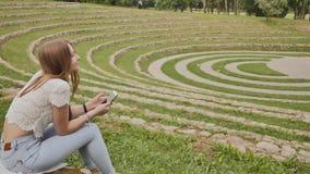一个年轻女学生在她的手上在体育场的边缘坐草并且拿着一个手机 休息在期间 影视素材