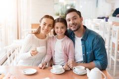 一个年轻家庭在咖啡馆一起来了 库存图片