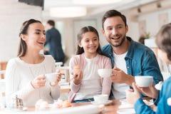 一个年轻家庭在咖啡馆一起来了 免版税库存图片