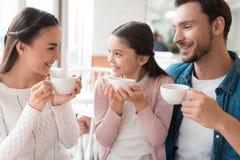 一个年轻家庭在咖啡馆一起来了 库存照片