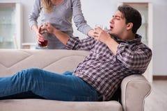 一个年轻家庭观念的饮用的问题被喝的丈夫人 免版税库存图片