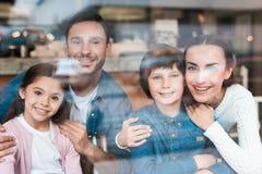 一个年轻家庭通过在咖啡馆的玻璃被拍摄 库存照片
