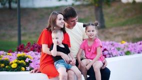 一个年轻家庭,包括4个人,在公园坐在美丽的花旁边 影视素材