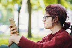 一个年轻少年女孩的画象有智能手机的在夏天城市公园 库存照片