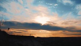 一个年轻徒步旅行者女孩的剪影有一个背包的在日落的顶面山 影视素材