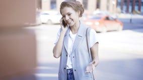 一个年轻微笑的女孩有一个电话外面户外 免版税库存照片