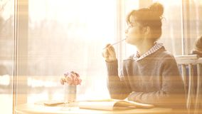 一个年轻微笑的深色的女孩的乌贼属照片看对窗口咖啡馆 免版税库存图片