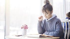 一个年轻微笑的深色的女孩读在咖啡馆的一个笔记本 免版税库存照片