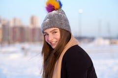 一个年轻快乐的女孩的晴朗的冬天照片在冬天帽子、围巾、外套和手套穿戴了 免版税库存图片