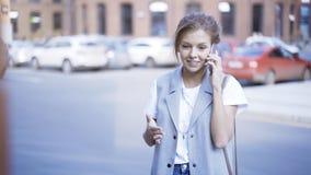 一个年轻恼怒的俏丽的女孩有一个电话外面户外 免版税库存图片