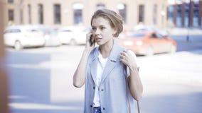 一个年轻恼怒的女孩有一个电话外面户外 免版税库存照片