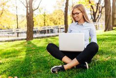 一个年轻惊人的夫人的图象,坐在公园,使用手提电脑,坐绿色草坪 免版税库存图片