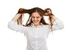 一个年轻愉快的女孩的画象白色背景的,在一件白色女衬衫 免版税库存照片