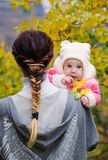 一个年轻愉快的母亲在肩膀拿着她的小女儿 免版税库存图片