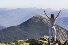 一个年轻愉快的美丽的亭亭玉立的女孩的剪影有站立在举手的山的大岩石的长的辫子的,遇见raisi 免版税库存图片
