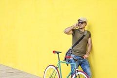 一个年轻成人人的侧视图有站立反对黄色墙壁一会儿的葡萄酒自行车的和佩带的便服和太阳镜 免版税库存照片