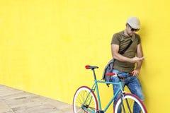 一个年轻成人人的侧视图有站立反对黄色墙壁一会儿的葡萄酒自行车的和佩带的便服和太阳镜 免版税图库摄影