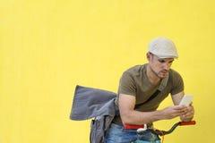 一个年轻成人人的侧视图有站立反对黄色墙壁一会儿的葡萄酒自行车的和佩带的便服和太阳镜 库存图片