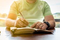 一个年轻成功的人在一本个人学报上的采取笔记 库存照片