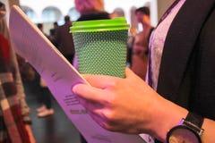 一个年轻成功的女孩的画象,饮用的咖啡,当与纸一起使用时 图库摄影