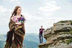 一个年轻新娘的画象一件五颜六色的礼服的有野花花束的在站立在背景的自然的  库存图片