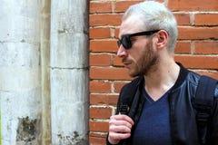 一个年轻有胡子的人佩带的太阳镜和看在手表 免版税图库摄影