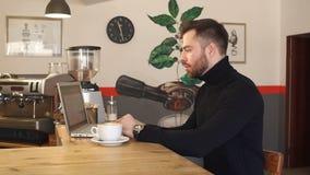 一个年轻有胡子的人商人的画象在咖啡馆,他研究膝上型计算机 影视素材