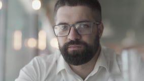 一个年轻有胡子的人的特写镜头戴眼镜的 一个人的画象戴看照相机的眼镜的 日志伽玛 股票录像