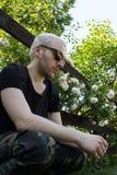一个年轻有胡子的由开花的庭院篱芭的人佩带的太阳镜  看的人坐由篱芭和下来 免版税图库摄影