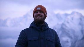 一个年轻有胡子的男性旅客的画象在微明下在山 站立认为和微笑辩解 股票录像