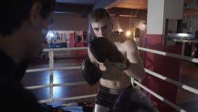 一个年轻欧洲人的特写镜头有体育的短缺与光秃的躯干,在圆环的被投入的拳击手套火车 股票录像