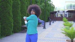 一个年轻正面的画象炫耀有一种非洲式发型的非裔美国人的妇女在背景  股票录像