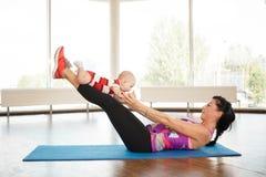 一个年轻母亲在一个小孩子帮助下震动她的腿 免版税库存图片